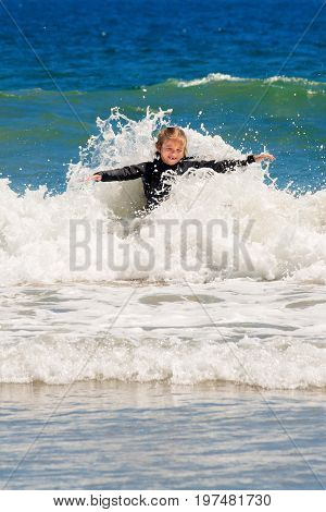 A young girl missing her front two teeth plays in the waves with water splashing all around her with her arms out.