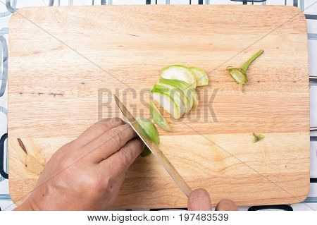 Hand cutting Thai Brinjal on wooden broad / Cooking green curry concept