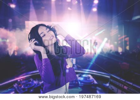 Image of pretty DJ enjoying her song while playing music in the nightclub