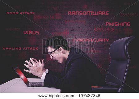 Concept of malware and computer virus. Stressful businessman screaming on a damaged laptop caused by virus