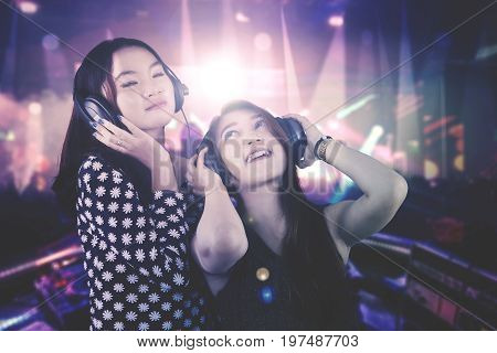 Photo of two beautiful DJ enjoys their song while playing music in the nightclub