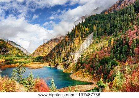 The Upper Seasonal Lake Among Colorful Fall Woods And Mountains