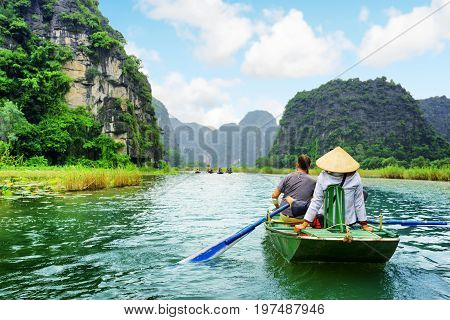 Tourists In Boat. Rower Using Her Feet To Propel Oars. Vietnam