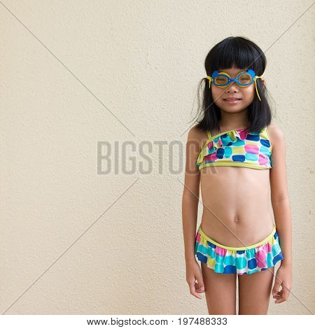 Little girl wearing swimming suit and goggles ready to swim