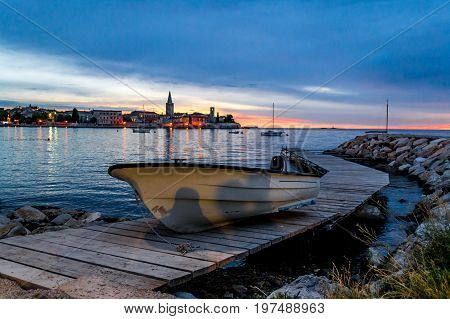 Lonely boat on a jetty at sunset with a Mediterranean old town in the background