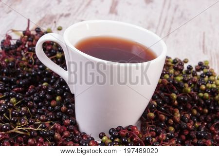 Cup Of Hot Tea With Elderberry Juice And Heap Of Berry