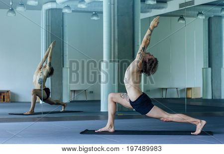 Handsome Tattooed Man Practicing Yoga. Young Male Teacher Taking Low Lunge Pose, Urdhva Ashva Sancha