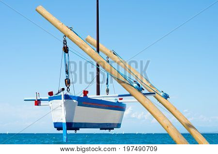 a hanging boat over the blue sea