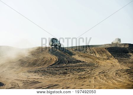 Desert safari on cars. Offroad jeeps driving on sand hill on grey sky background. Dune bashing. Extreme activity. Travel travelling. Discovery and adventure. Vacation and wanderlust