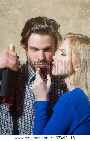 Girl drinking red liqueur from glass with macho with wine bottle. Girlfriend and boyfriend relaxing on beige background. Couple in love. Alcohol and appetizer. Unhealthy lifestyle and bad habits
