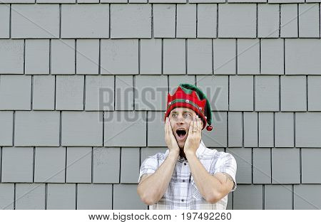Shocked man with Christmas hat on and a grey background.