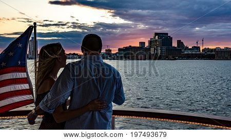 Baltimore Maryland USA - July 8 2017: A couple enjoys the view of the Baltimore Inner Harbor skyline on a sunset cruise.