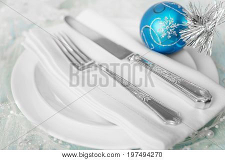 Christmas table with white plates linen napkin silver knife and fork and a beautiful blue Christmas ball