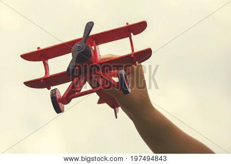 Child Hand Holding Wooden Handmade Airplane