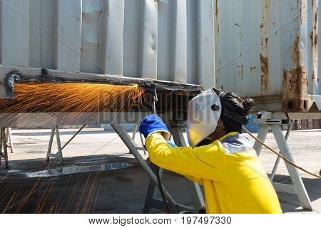 Industry worker with protective mask welding steel to repair container structures manufacture workshop. Worker welding in factory industry.