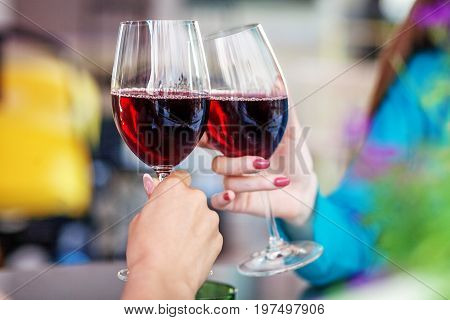 Glasses of red wine in their hands. Toast. The concept of party and celebration.