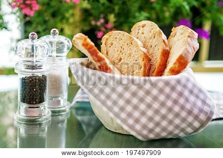 Basket with bread. Salt and pepper on the table. The concept is healthy food and vegetarianism.