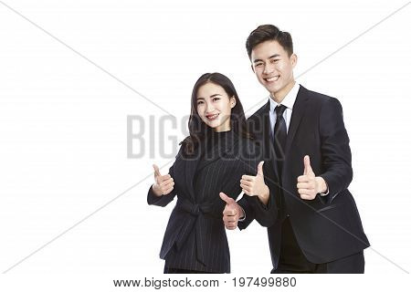 pair of asian business people in formal wear showing two-thumb-up sign looking at camera smiling isolated on white background.