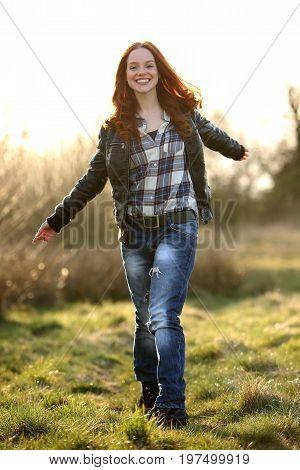 Beautiful redhead woman walikng on gras smiling