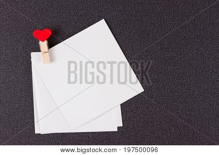White blank cards on rope love notice backdrop. small sheets of paper on clothespin with red hearts bright memo background