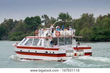 CAMARGUE, FRANCE - JUNE 22, 2017: Touristic boat with passengers on Rhone River, Camargue Park, France