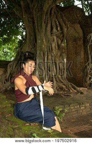 Pretty Asian woman draping in Thai traditional warriors at Gate of time of ancient temple in Ayutthaya Historical Park , Middle of Thailand.
