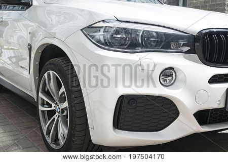 Sankt-Petersburg Russia July 21 2017 BMW X5 M Perfomance. Tire and alloy wheel. Headlight. Front view of a white modern luxury car. Car exterior details