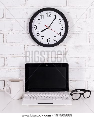 Workplace At Home Or In Office - Modern Laptop, Glasses, Cup Of Coffee And Office Clock