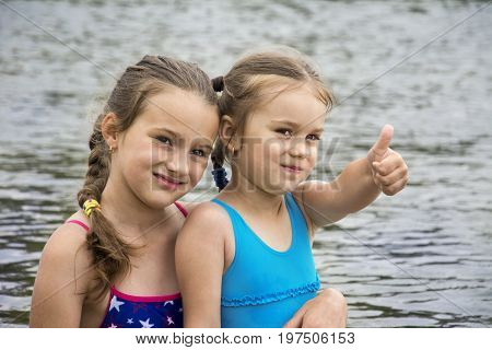 In the summer on the river two sisters show by hand that everything is fine.