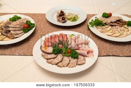 Cold Meat Plate With Delicious Sliced Ham, Prosciutto, Meat And Vegetables On Celebratory Dinner Tab