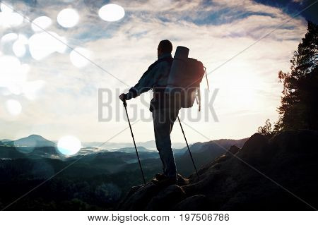 Film Grain. Tourist Guide On The Way With Pole In Hand. Hiker With Sporty Backpack Stand On Rocky Vi