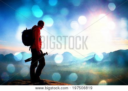 Film Grain. Tall Adult  Photographer Think About Picture At Sunset In The Misty Mountains