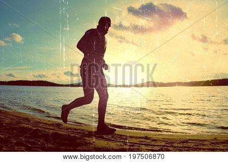 Film Grain. Tall Man With Sunglass And Dark Cap Is  Running On The Beach At Sunset