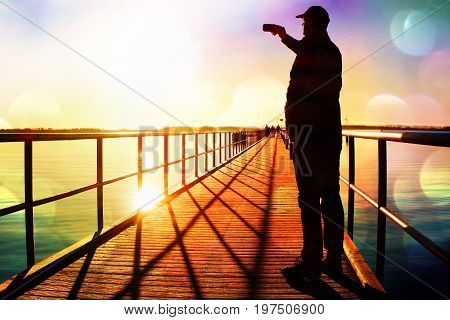 Film Grain. Man On Pier Photograph Morning Sea. Tourist With Smart Phone In Hand. Fantastic Morning