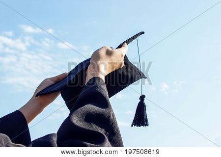 Graduate celebrating with cap in her handfeeling so proud and happiness in Commencement day
