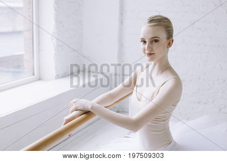 Beautiful ballerina standind at barre near the window in a classroom crossing her arms and putting them on barre. She is taking a short break between the exercises. Girl is looking at the camera. Close up.