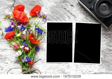 Retro camera and blank paper photo frames on wooden table with summer wildflowers. concept of remembrance and nostalgia in autumn. mock up