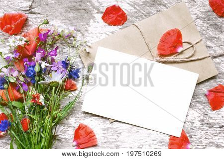 blank white greeting card with wildflowers bouquet and envelope with flower petals on white wooden background. vintage toning.top view. mock up