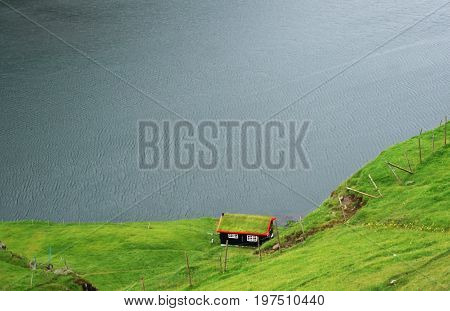 a small traditional house with a roof covered with grass in the mountains of Faroe Islands among green meadow on the coast of dark-blue atlantic ocean
