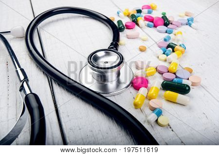 Pharmacy background on a white table. Tablets on a white background. Pills. Medicine and healthy. Close up of capsules. Stethoscope on a white wooden background. Copy space for a text.