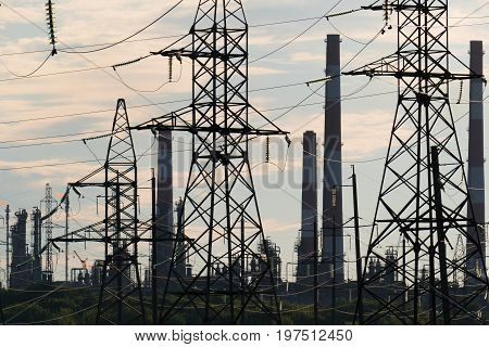 industrial landscape with power lines in the background pipes refinery.