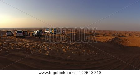 Dubai United Arab Emirates - January 4 2015: Tourists enjoy a four-wheel drive safari tour in Dubai desert at beautiful sunset.