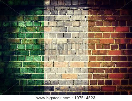 Faded Irish flag on a brick wall background with a dark vignette