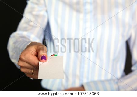 Young businesswoman girl holds out business card.