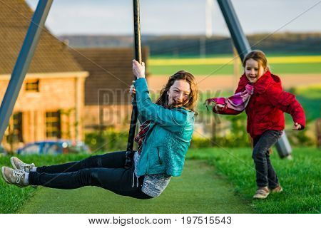 Two Sisters: Preschooler And Teenage - Playing On Playground
