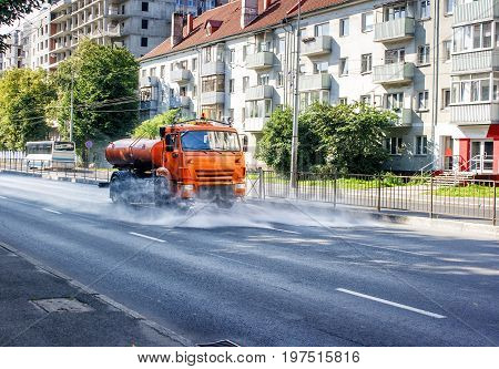 cleaning sweeper machine washes the city asphalt road with water spray on summer morning