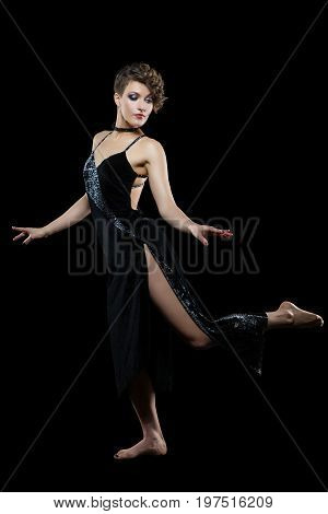 beautiful young woman dancer unblock tango dress on black background. copy space.