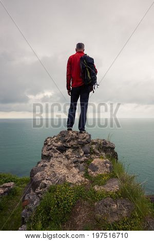 Traveler Stands On A Cliff And Looks At The Sea