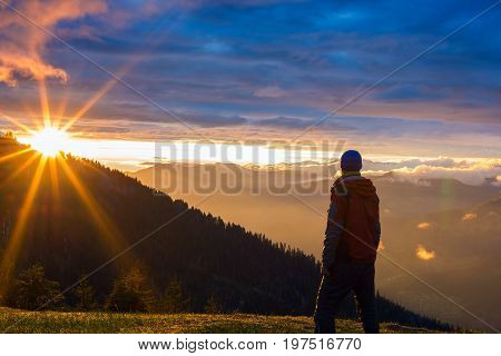 Lonely Traveler Stands In The Mountains, During The Sunset