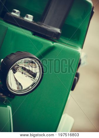 Industrial details mechanical objects and tools concept. Reflector on big heavy green vehicle
